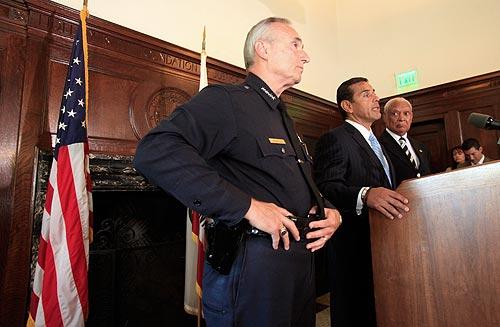 LAPD Chief William J. Bratton listens as Mayor Antonio Villaraigosa announces Bratton's resignation. At right is John Mack, a member of the Police Commission.