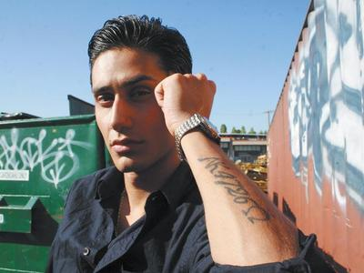 Former gang member Amir Javid shows his tattoo in Vancouver yesterday. He said he would get it removed if the RCMP pays for it.